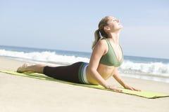 Женщина работая на циновке йоги на пляже Стоковая Фотография