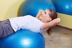 Женщина работая на шарике гимнастики Стоковая Фотография