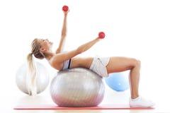 Женщина работая на шарике фитнеса стоковое изображение