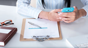 Женщина работая на celphone, сидя на столе Стоковые Фотографии RF