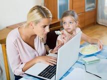 Женщина работая от дома, маленькая дочь прося внимание Стоковые Изображения