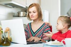 Женщина работая от дома, маленькая дочь прося внимание Стоковое фото RF