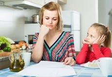 Женщина работая от дома, маленькая дочь прося внимание Стоковое Изображение RF