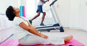 Женщина работая пока человек jogging на третбане 4k видеоматериал