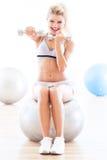 Женщина работая с гантелями на шарике фитнеса стоковое изображение rf