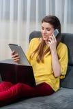 Женщина работая с компьтер-книжкой и мобильным телефоном Стоковая Фотография
