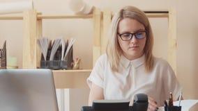 Женщина работая с компьютером в офисе и выборах вверх телефон видеоматериал