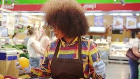 Женщина работника супермаркета Афро-американская с афро стилем причесок сортирует плод медленный mo видеоматериал