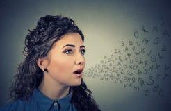 Женщина разговаривая с алфавитом помечает буквами приходить из ее рта черный телефон приемника принципиальной схемы связи стоковая фотография