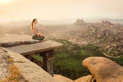Женщина размышляя на скалистой горе на восходе солнца, Индии Стоковые Фотографии RF