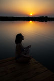 Женщина размышляет в заходе солнца на деревянном доке Стоковое Изображение