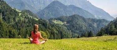 Женщина размышляет на горах Стоковое фото RF