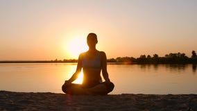 Женщина размышляя в лотосе представления над оранжевым солнцем
