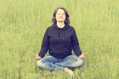Женщина размышляя в положении лотоса на зеленой траве Стоковое фото RF