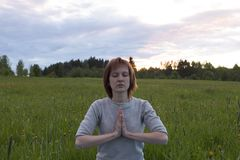 Женщина размышляя в представлении лотоса на заходе солнца Стоковая Фотография RF