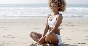 Женщина размышляя на пляже в положении лотоса видеоматериал