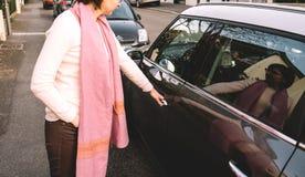 Женщина раскрывает дверь нового мини автомобиля на французской улице Стоковая Фотография RF