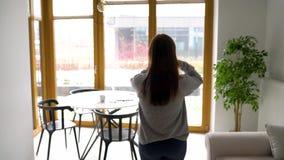 Женщина раскрывает окно в спальне и идет в комнату, сидит вниз на таблице и начинает ее рабочий день _