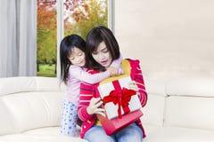 Женщина раскрывает подарок с ее дочерью Стоковое фото RF