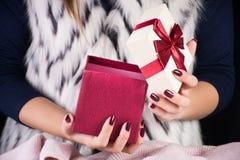 Женщина раскрывая коробку красного подарка присутствующую со смычком связи стоковые изображения