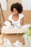 Женщина распаковывая коробки в ее новом доме стоковое изображение