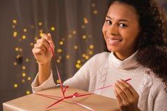 Женщина распаковывая подарок на рождество Стоковое Изображение