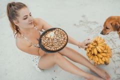 Женщина распологая на песок с тортом банана стоковое фото