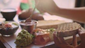Женщина распространяет томат над здравицей хлеба сток-видео