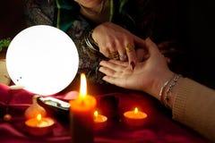 Женщина рассказчика удачи указывает ее палец к другой ладони женщины Стоковое Фото