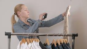 Женщина рассматривает и фотографирует, используя смартфон, lothing смертную казнь через повешение на вешалке акции видеоматериалы