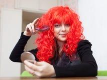 Женщина расчесывает красный парик Стоковые Фотографии RF