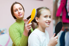 Женщина расчесывая волосы девушки Стоковая Фотография RF