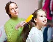 Женщина расчесывая волосы девушки Стоковые Изображения