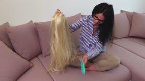 Женщина расчесывая парик белокурых волос видеоматериал