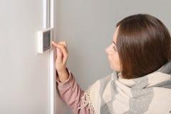 Женщина регулируя термостат на белой стене стоковая фотография
