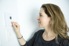 Женщина регулируя термостат на системе отопления домов Стоковое фото RF