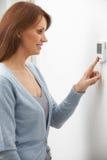 Женщина регулируя управление термостата центрального отопления Стоковая Фотография RF