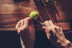 Женщина режа киви стоковые фотографии rf