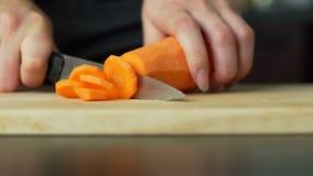 Женщина режа морковь видеоматериал