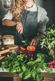 Женщина режа свежие зрелые томаты на конкретном счетчике кухни стоковая фотография rf