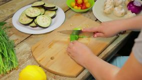Женщина режет зеленые перцы chili с ножом на деревянной доске акции видеоматериалы