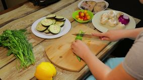 Женщина режет зеленые перцы chili с ножом на деревянной доске сток-видео