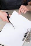 Женщина режет лист бумаги с парой ножниц Стоковые Изображения RF