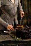 Женщина режет конец шоколадного торта Темные тоны стоковое фото rf