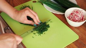 Женщина режет свежий укроп в кухне на деревянном столе акции видеоматериалы