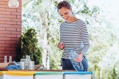 Женщина рециркулируя пластичную бутылку Стоковые Изображения