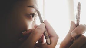 Женщина рисуя ее бровь стоковая фотография rf