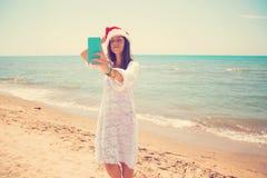 Женщина рождества молодая усмехаясь в красной шляпе santa принимая автопортрет изображения на smartphone на пляж над предпосылкой стоковые изображения rf