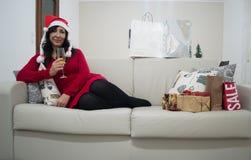 Женщина рождества Санты ослабляя на софе Стоковая Фотография RF