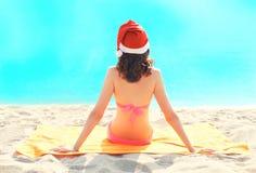 Женщина рождества в сидеть красной шляпы santa ослабляя на пляже песка над морем Стоковое Изображение